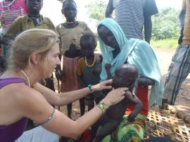 Allison Fowler, CMF missionary working in Ethiopia, examines a sick Gumuz baby on a visit to the village of Neger.