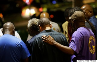 Worshippers gather to pray in a hotel parking lot across the street from the Emanuel AME Church following a shooting Wednesday, June 17, 2015, in Charleston, S.C. (AP Photo/David Goldman)